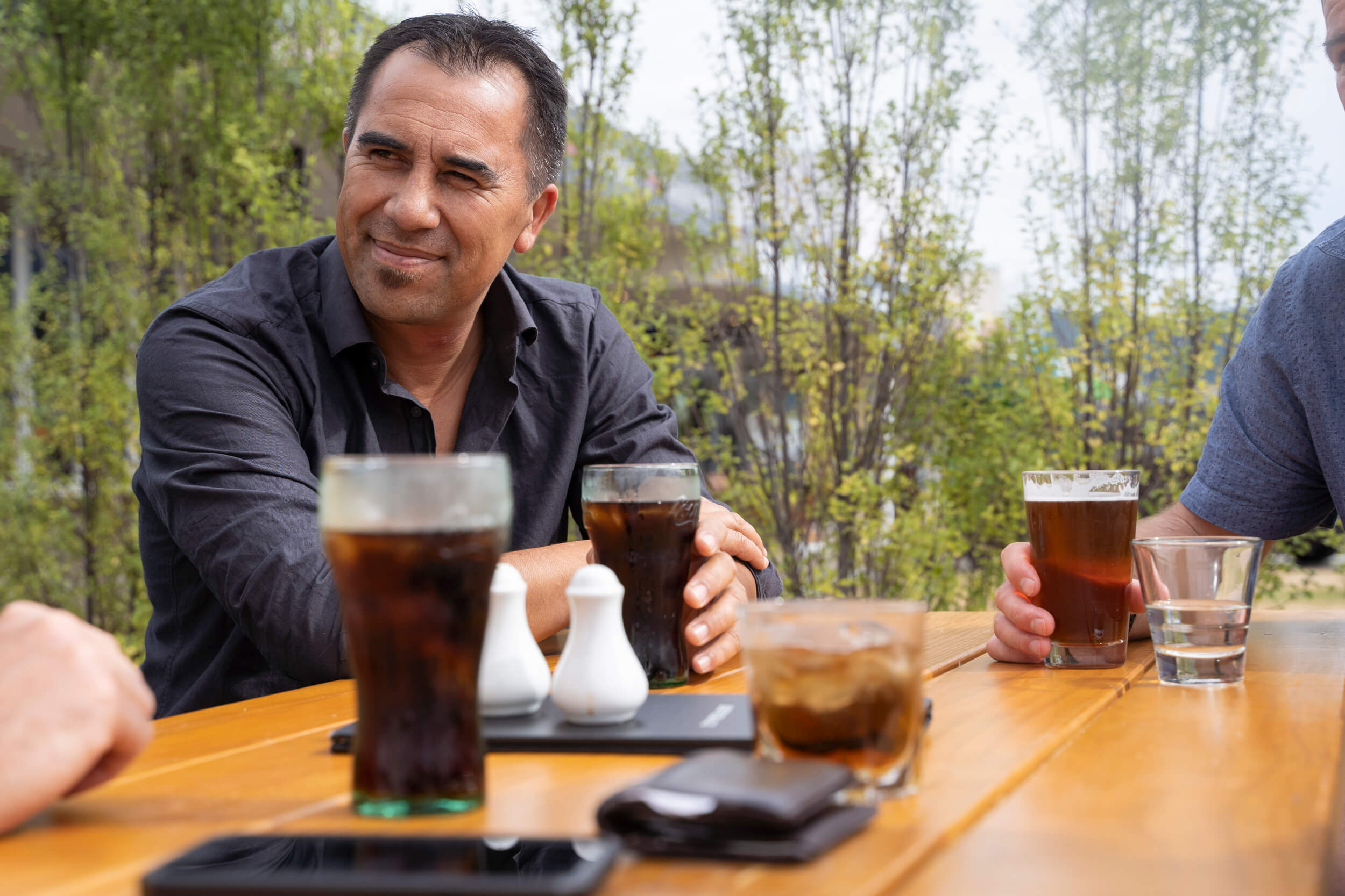 Man sitting at a wooden table listening and enjoying drinks with his companions.