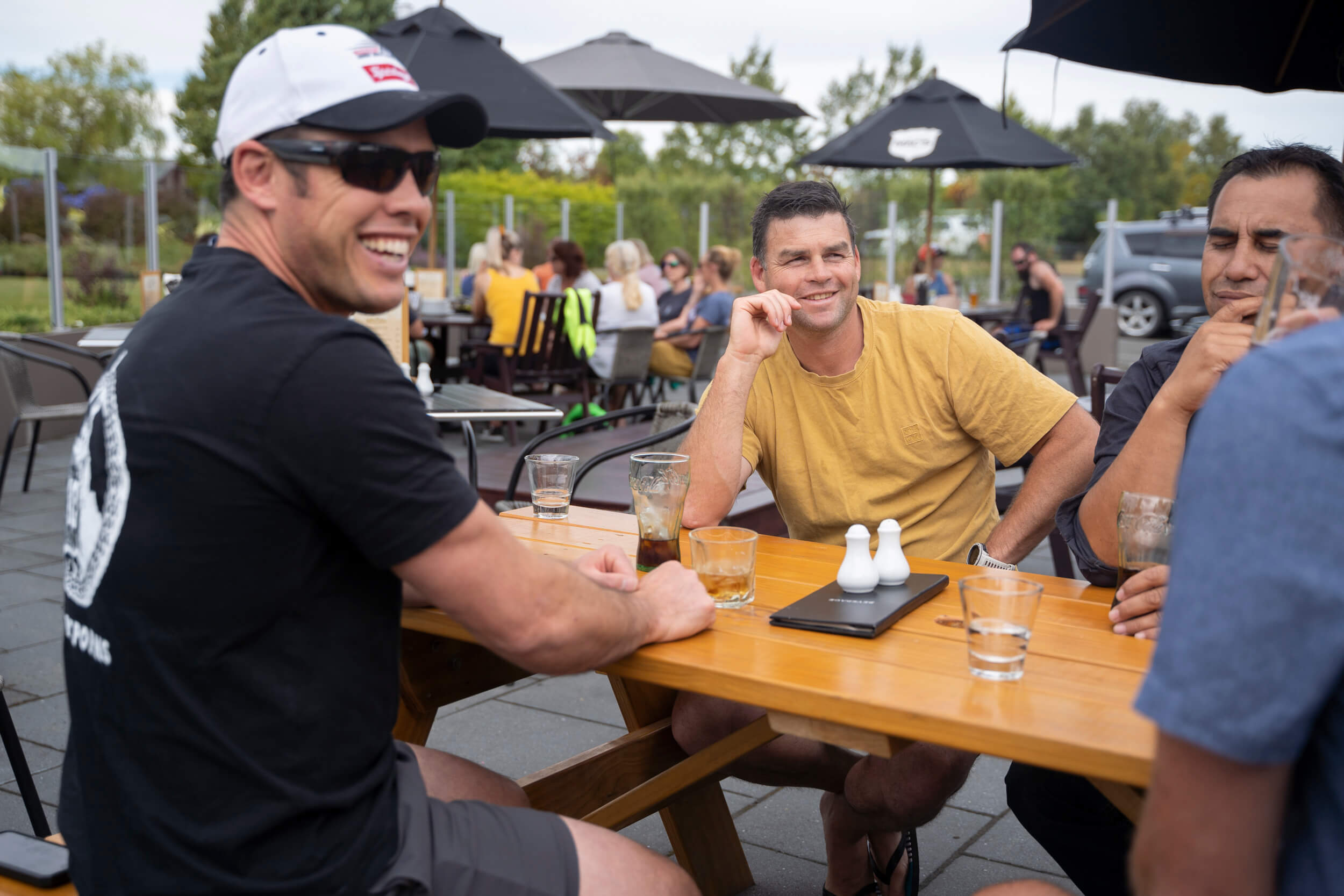 Three men sitting at a table outside Te Anau restaurant enjoying a drink